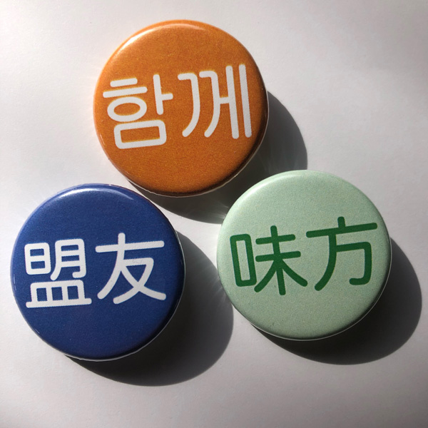 orange, purple and green pins that say ally in Chinese, Korean and Japanese